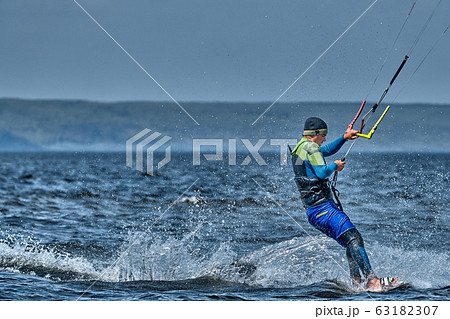 A male kiter slides on the surface of the water. 63182307