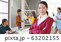 Portrait of beautiful Asian woman smiling in modern office, with young creative team work together 63202155