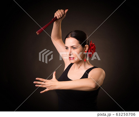 Expressive woman dance flamenco under dramatic light. Attractive lady with red rose in hair and in black dress hold a fan in hand like a knife, portrait, low key. 63250706