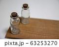 白い机の上に置かれた小瓶 63253270