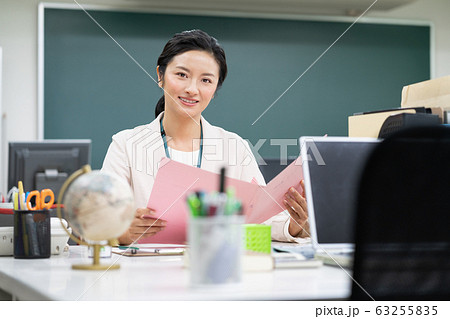 職員室で書類に記入するミドルエイジの女性教師 63255835