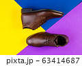A pair of brown leather boots on color paper background. 63414687
