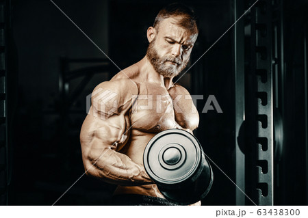 Bodybuilder strong man pumping up biceps muscles 63438300