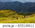 草紅葉の巻機山稜線を行くハイカー 63518911