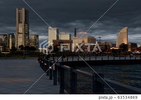 真っ黒な雲をバックに、夕陽が当たる横浜のビル 63534869