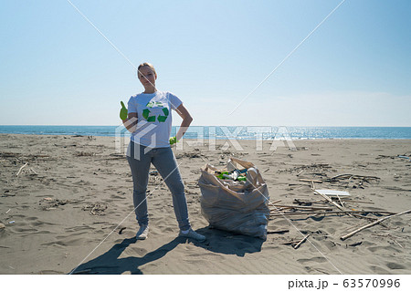 woman picks up trash from the beach in trash bags 63570996