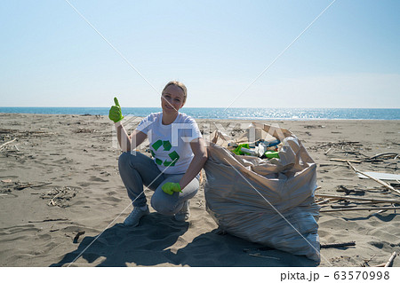 woman picks up trash from the beach in trash bags 63570998
