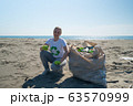 woman picks up trash from the beach in trash bags 63570999
