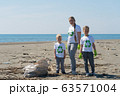 family picks up trash from the beach in trash bags 63571004