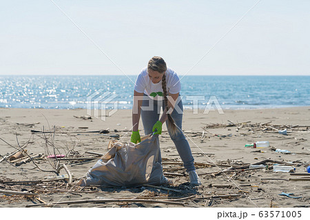 woman picks up trash from the beach in trash bags 63571005
