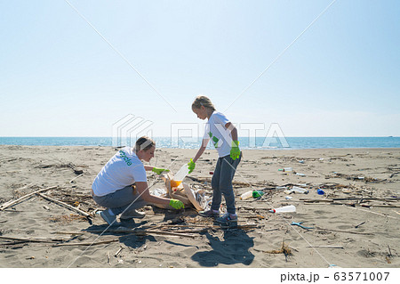 mother and daughter removes the debris from the beach in garbage bags 63571007