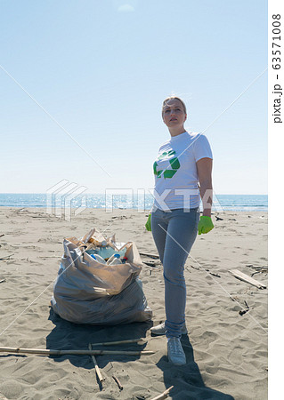 woman picks up trash from the beach in trash bags 63571008