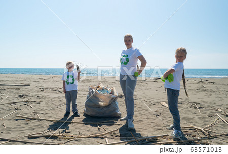 family picks up trash from the beach in trash bags 63571013