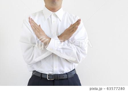 両腕でバツをしているワイシャツを着た男性 63577280