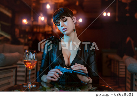 Sexy young woman with a gun. 63629601