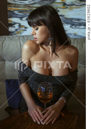Attractive young woman holds a glass of wine. 63629602