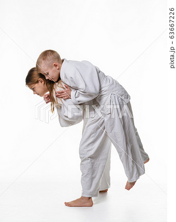 Judo student girl learns to perform throw through 63667226