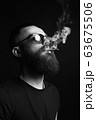 handsome bearded smoking man in glasses 63675506
