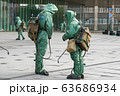 COVID-19 outbreak. Two medical workers in bio viral hazard protective suits spray of chemicals for 63686934