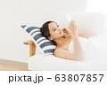 寝転がってスマホを使う笑顔の女性 63807857