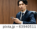 若いビジネスマン(会議室、スーツ、スマホ 63940511