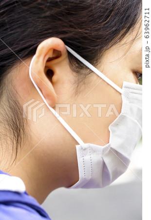 白いマスクをした女性の横顔のアップ 63962711
