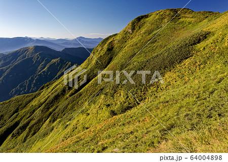 秋色の越後三山・中ノ岳山頂と朝の山並み 64004898