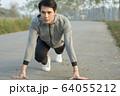 スタートポーズをとる若い男性 64055212
