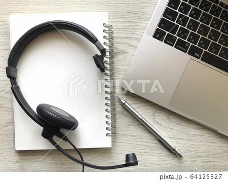 ノートパソコンとヘッドセットとノートとペン(木目背景)、リモートーワーク・テレワークイメージ 64125327