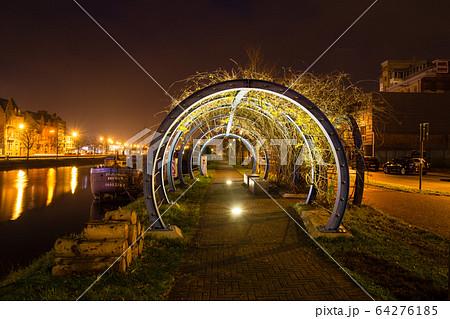 ベルギーのブルージュの街並みの夜景 川沿いに作られた石畳の歩道とライトアップされたトンネル 64276185