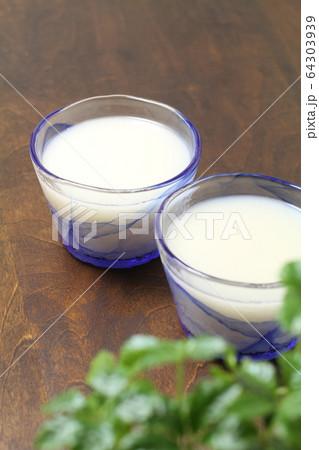 涼しげなグラスに入った二個の冷やし甘酒、観葉植物 64303939
