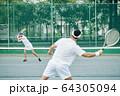 Female tennis player hitting ball 64305094