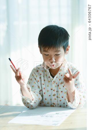 指を使って計算する小学生の男の子 64306767