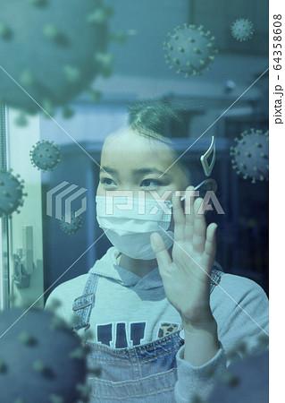 窓辺に立って外を見るマスク姿の小学生女の子 漂うウイルス 64358608