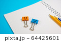 Orange Color and Blue Smile Binder Clips with Pencils on Notepad 64425601