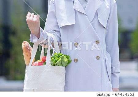 スーパーマーケットで買物した食品をエコバッグに入れてもつ若い女性の手元 64454552