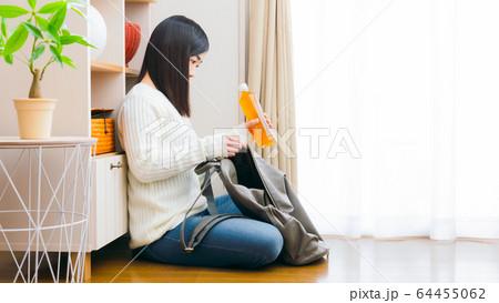 ペットボトル飲料をリュックに入れる女性 お茶 コピースペース 16:9 64455062