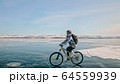 Woman is riding bicycle on the ice. Tires on bike are covered wi 64559939