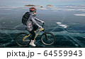 Woman is riding bicycle on the ice. Tires on bike are covered wi 64559943