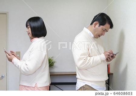 反対方向をむいてスマホを操作する中高年男女 64608603