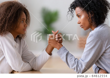Serious african american mom and teen daughter arm wrestling 64612554