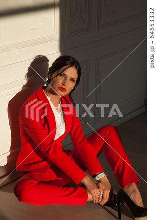 Portrait of a brunette woman in a red business suit on the floor 64653332