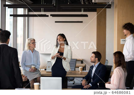 Serious asian coach speaking at diverse corporate group meeting 64686081
