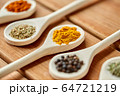 spoons with different spices on wooden table 64721219