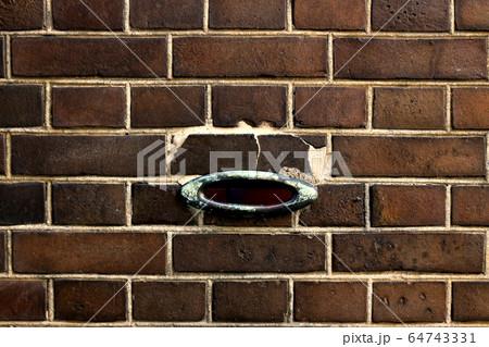 古いレンガ造りの壁に開けられたアンティークなデザインの郵便受けの投入口 64743331