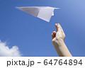 紙飛行機を飛ばす子供手元 64764894