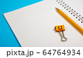 Blank Paper Notepad with Orange Color Pencils and Smile Binder Clip on Blue Background 64764934