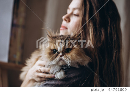Girl communicates with her domestic red fluffy cat. Love for animals. 64791809