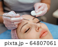 mechanical cleaning of the face around the nose patient spa salon using an extractor 64807061