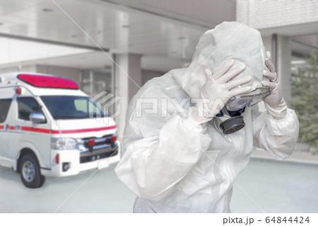 病院エントランスで救急車をバックに頭を抱える防護服の医療従事者 64844424